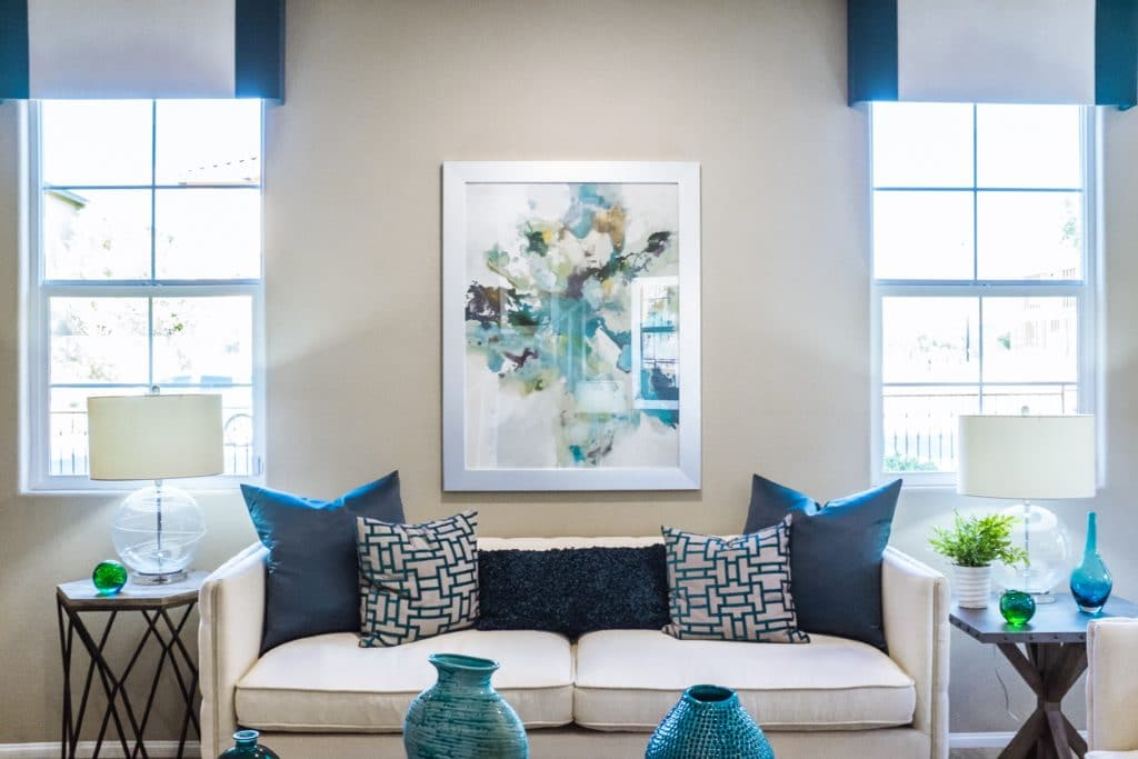 Sitting room showcasing a couch in the center with blue decorative accents around the room.