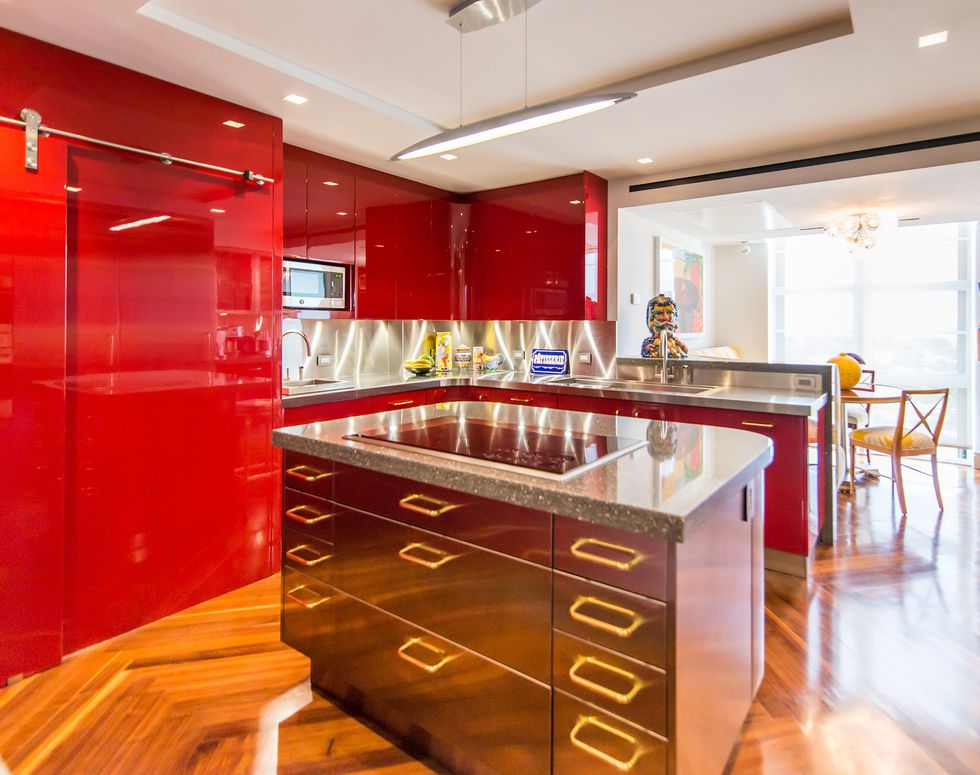 Bright kitchen with shiny red cabinets and coper island.