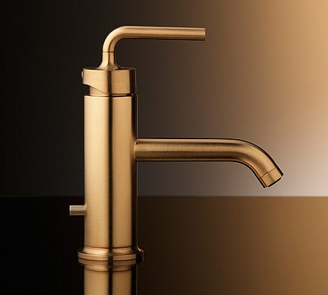 Gold sink spout in a bathroom.