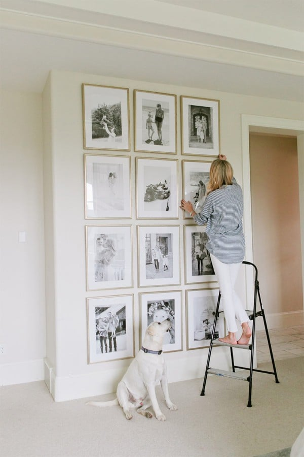 Woman arranging framed photos on a wall in her home.