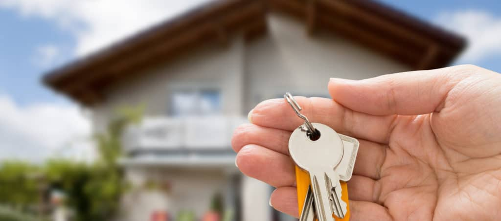 Person holding keys to their new home after purchase on the real estate market.